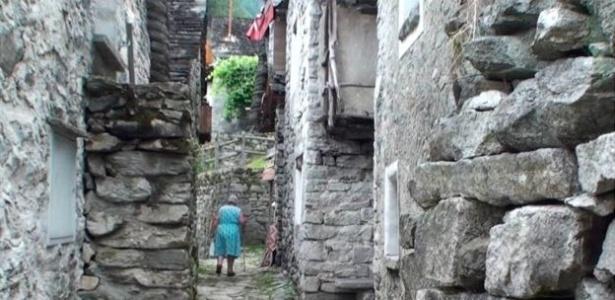 senhora-caminha-por-uma-rua-estreita-de-corippo-ladeada-por-construcoes-de-pedra-1504817291487_615x300