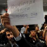 """Deputado Jair Bolsonaro levanta cartaz onde se lê """"queimar rosca todo dia"""" e mostra aos manifestantes contrários ao presidente da comissão, deputado Marco Feliciano, durante sessão da Comissão dos Direitos Humanos"""